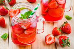 Strawberry lemonade with lime and ice in mason jar Stock Photos