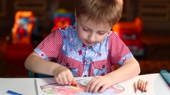 Boy Paints the Car With Crayons Sitting at Table - stock footage