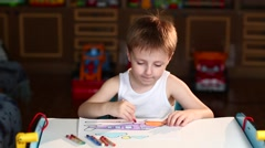 Boy Paints the Plane With Crayons Sitting at Table - stock footage