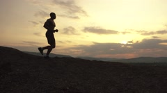 Side view on silhouette of african american athlete jogging on sunset on the Stock Footage