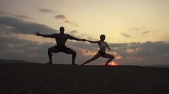 Silhouettes of athletic muscular couple of fitness instructors doing gymnastic - stock footage