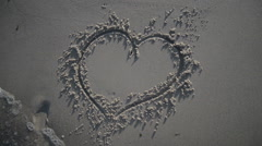 Heart Being Washed Away On Sandy Beach Stock Footage