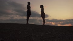 Silhouettes of fit mixed race couple stretching together on the rocky mountains Stock Footage
