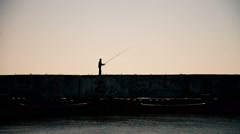 A man fishing from the breakwaters wall with industrial background during sunset Stock Footage