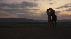 Silhouettes of athletic muscular mixed race couple watching the sunrise in Stock Footage