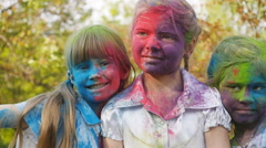 Cute european child girls celebrate Indian holi festival with colorful paint Stock Footage