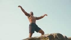 Muscular strong black bodybuilder posing on the rock against blue cloudy sky - stock footage