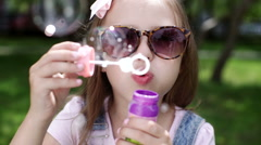 Little girl blowing soap bubbles in summer park. Stock Footage