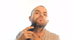 Man shaves beard electric razor on a white background. Stock Footage