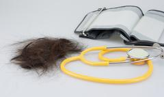 Lost hair with stethoscope and sphygmomanometer - stock photo