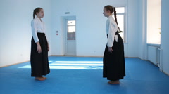 Two girls in black hakama practice Aikido Stock Footage