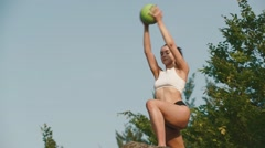 Sexy brunette woman fitness instructor doing exercises with ball. Outdoor Stock Footage
