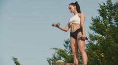 Sexy brunette athlete woman doing exercises with dumbbells and ball. Outdoor Stock Footage