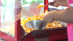 4K, A static shot of a commercial popcorn machine. Mixing by human hand Stock Footage