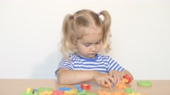 Child little girl playing plastic constructor toys at home Stock Footage