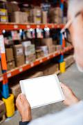 Rear view of warehouse manager looking his tablet computer in a depot Stock Photos