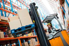 Warehouse worker using forklift in warehouse Stock Photos