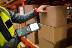 Focus on hand scanner in a warehouse Stock Photos
