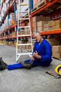 Worker lying and suffering on the floor in warehouse Stock Photos