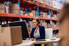 Warehouse manager working on her computer desk in a depot Stock Photos
