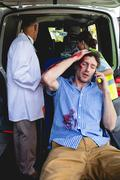 Injured man on the phone with ambulance men behind front of an ambulance car Stock Photos