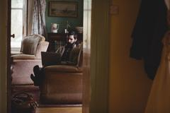 Hipster man using computer in the couch in country house Stock Photos