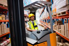 Warehouse manager driving a forklift in warehouse Stock Photos