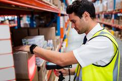 Warehouse manager with yellow coat scanning barcode on box in warehouse Stock Photos