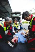 Injured man being healed by a team of ambulancemen front of ambulance car Kuvituskuvat