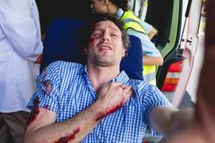 Injured man taking selfie front of ambulance car Kuvituskuvat