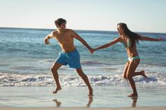 Happy young couple holding hands and running on beach - stock photo