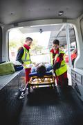 Injured man with ambulance men front of ambulance car Kuvituskuvat