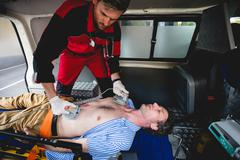 Ambulance man using defibrillator in the ambulance car Kuvituskuvat
