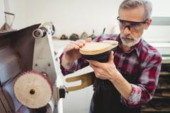 Cobbler touching the sole of a shoe in his workshop Stock Photos