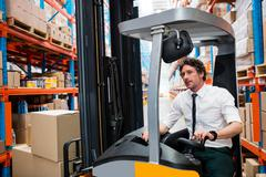 Warehouse manager using a forklift in warehouse Stock Photos