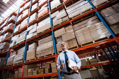 Low angle view of warehouse manager holding a clipboard in a depot Stock Photos