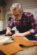 Concentrated cobbler drawing shoes with his blade Stock Photos