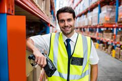 Smiling warehouse manager with yellow coat and scanner in warehouse Stock Photos