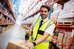 Manager with yellow coat preparing a shipment in warehouse Stock Photos