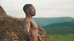 Close-up of handsome african american bodybuilder stretching outdoor. Mountain - stock footage