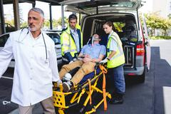 Injured man with ambulance men in ambulance car Stock Photos