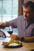 Portrait of mature man filling a glass of wine in his country house Stock Photos