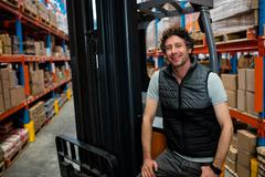 Warehouse worker with forklift in background in warehouse Stock Photos