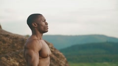 Side view of strong african american bodybuilder stretching outdoor. Mountain Stock Footage