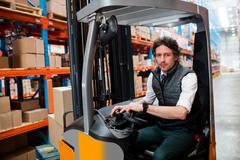 Portrait of a warehouse manager using a forklift in warehouse Stock Photos