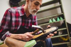 Cobbler hammering on the sole of a shoe in his workshop - stock photo