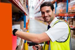 Smiling warehouse manager with yellow coat scanning barcode on box in warehou Stock Photos