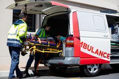 Ambulance men bringing injured people inside ambulance car Kuvituskuvat