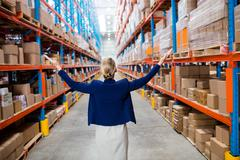 Rear view of warehouse manager raising her arms in a depot Stock Photos