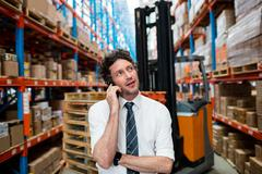 Warehouse manager giving phone call next to a forklift in warehouse Stock Photos